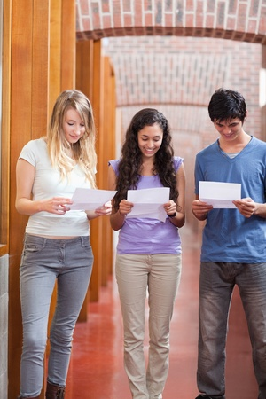 Portrait of students reading a piece of paper in a corridor Stock Photo - 11181425