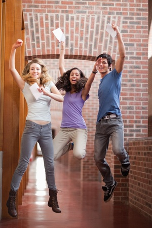 test result: Portrait of successful students jumping in a corridor Stock Photo