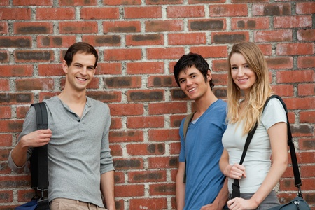 Smiling students posing outside a building photo
