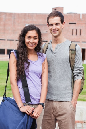 Portrait of a smiling student couple posing outside building Stock Photo - 11182017