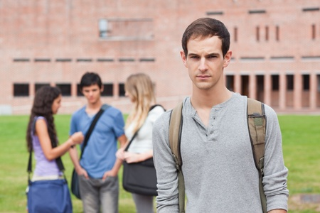 friendless: Lonely male student posing while his classmates are talking outside a building