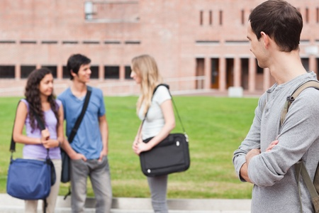 Student looking at his classmates talking outside a building photo
