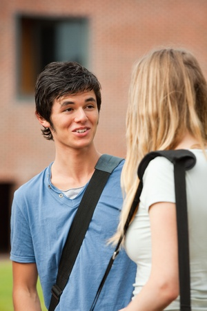 Portrait of a surprised student talking with a friend outside a building Stock Photo - 11182833