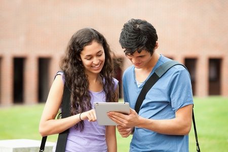 studious: Couple using a tablet computer outside a building Stock Photo