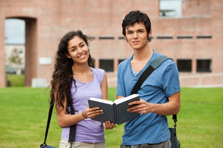 Couple holding a book outside a building photo
