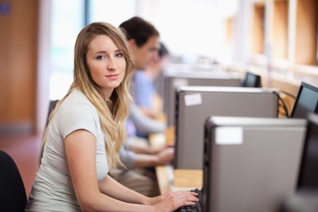 Blonde student using a computer in an IT room photo