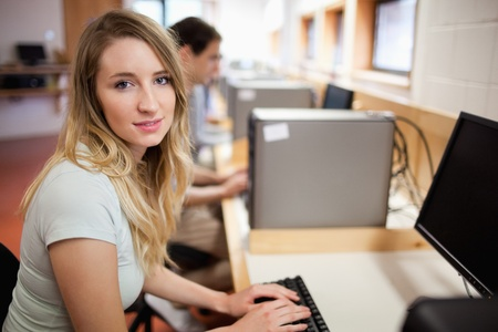 Student posing with a computer in an IT room Stock Photo - 11183649