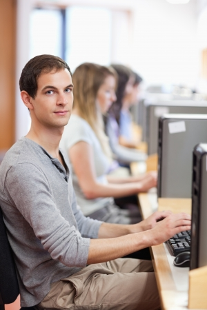 Portrait of a male student posing with a computer in an IT room photo