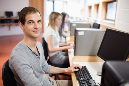 Smiling male student posing with a computer in an IT room photo