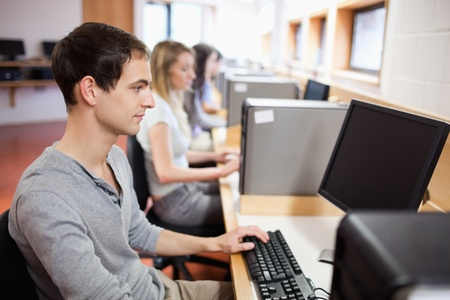 Serious male student working with a computer in an IT room photo