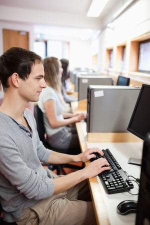 Portrait of a serious male student working with a computer in an IT room photo