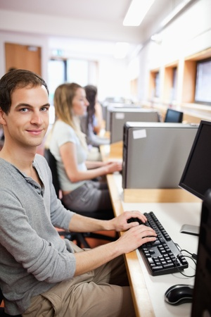 Portrait of a young male student posing with a computer in an IT room photo