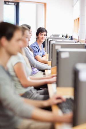 Portrait of young fellow students in an IT room with the camera focus on the background Stock Photo - 11183793