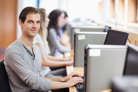 student desk: Smiling fellow students in an IT room with the camera focus on the foreground Stock Photo