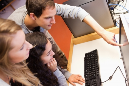 Fellow students using a computer in an IT room photo