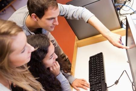 estudiantes universitarios: Sus compa�eros usando una computadora en una sala de TI