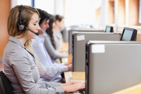 Operators using a computer in call center with the camera focus on the foreground
