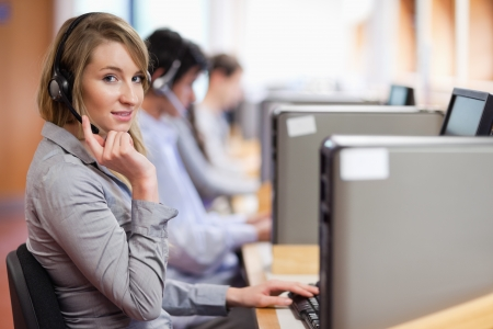 personal call: Blonde operator posing with a headset in a call center