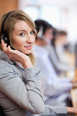 Portrait of a blonde operator posing with a headset in a call center photo