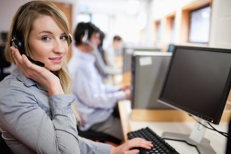 personal call: Smiling blonde operator posing with a headset in a call center