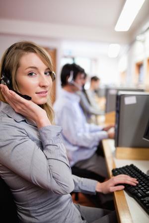 Porträtt av en leende blond operatör poserar med ett headset i ett call center