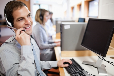business centre: Smiling assistant using a headset in a call center Stock Photo