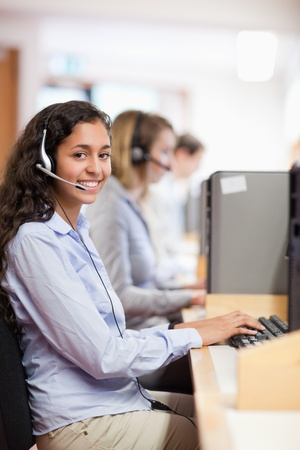 Portrait of a smiling assistant working with a computer in a call center photo