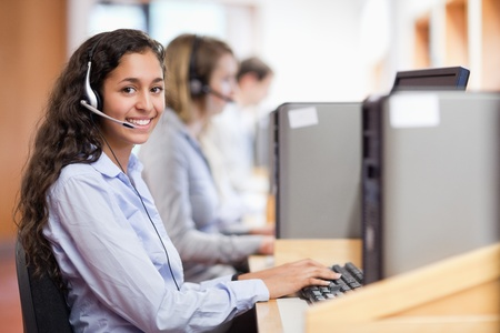 Smiling assistant working with a computer in a call center photo