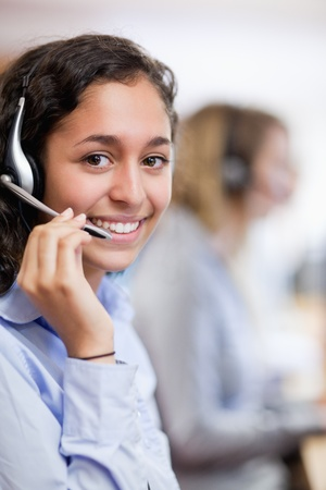 Portrait of a smiling customer assistant wearing a headset photo