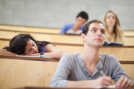 prestar atencion: Los estudiantes escuchan un profesor, mientras que su compañero está durmiendo en un anfiteatro