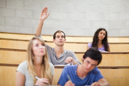college classroom: Student raising his hand while his classmates are taking notes in an amphithater Stock Photo