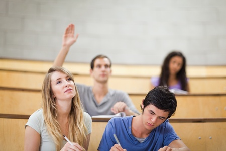 Students taking notes while their classmate is raising his hand in an amphitheater photo