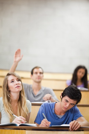 Portrait of students taking notes while their classmate is raising his hand in an amphitheater photo