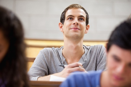 Smiling student listening to a lecturer in a amphitheater photo