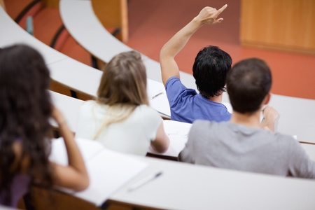 pay raise: Young student raising his hand while his classmates are taking notes in an amphithater