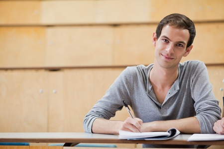 Male student holding a pen in an amphitheater photo