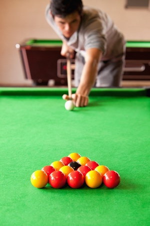 poolball: Portrait of a man playing snooker with the camera focus on the balls