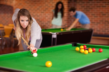 poolball: Woman playing snooker in a student home Stock Photo