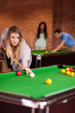 Portrait of a student woman playing snooker in a student home photo