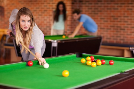 Student woman playing snooker in a student home photo