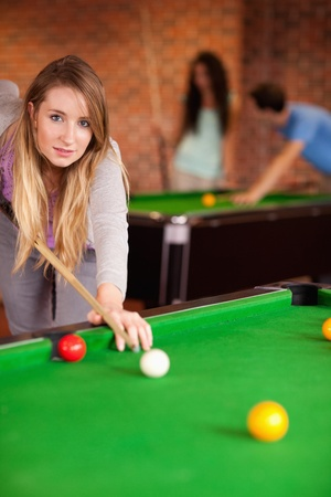 Portrait of a young woman playing snooker in a student home photo