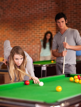 Portrait of friends playing snooker in a student home photo