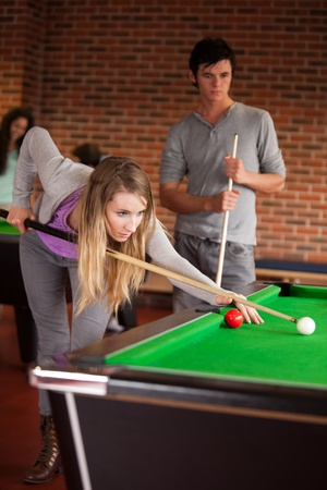 Portrait of young friends playing snooker in a student home photo