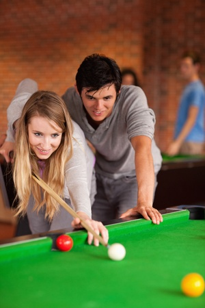 snooker cue: Portrait of a couple playing snooker in a student home