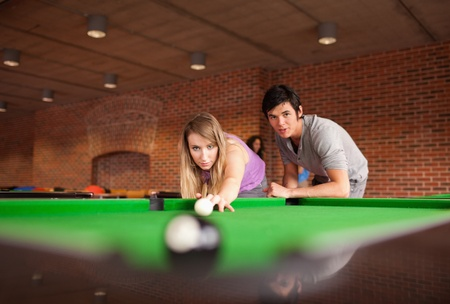 Man teaching pool to his girlfriend with the camera focus on the models photo
