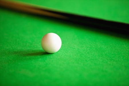 Close up of a queue ball and a queue against a green background photo