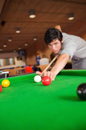 poolball: Portrait of a student playing pool in a student home