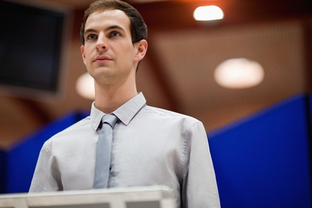 auditorium: Young man doing a presentation looking away from the camera