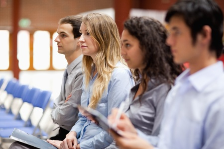 Business people listening and taking notes during a presentation photo