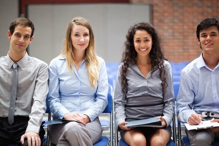 Business people sitting on chairs during a presentation photo